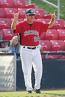 Hickory Crawdads manager Bill Richardson #24 signals that there are 2 outs against the Rome Braves at  L.P. Frans Stadium May 23, 2010, in Hickory, North Carolina.  The Rome Braves defeated the Hickory Crawdads 5-1.  Photo by Brian Westerholt / Four Seam Images