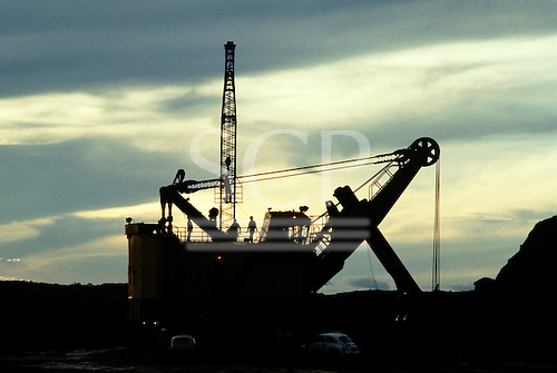 Carajas, Brazil. Large mechanical shovel with men on top in silhouette against the sky; iron ore mine, Para State.