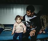 Niaz Mohammed Khawari, 35 mit seiner Tochter (2), sie hat eine Herzschwäche, seit sie auf der Flucht waren, seit drei Monaten im Lager; aus Daikondi, Afghanistan
