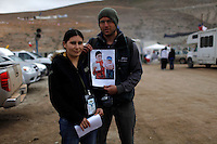 The wife of miner Alberto Molina, trapped in a tunnel 700 meters under the ground, pose for a picture with our photographer Lorenzo Moscia. Lorenzo made a print of Molina's wife and son, she wrote a message in the picture and rescue team manage to send  it to the miner through a tube.