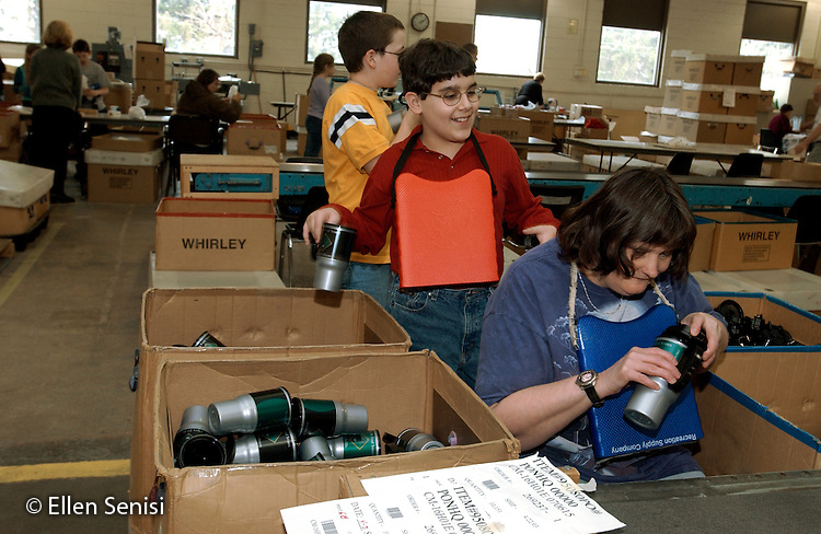 MR / Olean, NY /.Washington West Elementary School, Fifth Grade.Students (foreground: Boy, 11) work on assembly line task with adult partner in sheltered workshop day program for consumers with special needs.  Unique program called Friday Friends pairs adult consumers with special needs with school children. As part of a business-school partnership, consumers and students participate together in reading, crafts, and free time activities. The program's objective is to bring people with and without disabilities together regularly. It is supported by a local, annual fund raising event and hours contributed by volunteers..MR: Sco3   Han11   Sha2.© Ellen B. Senisi