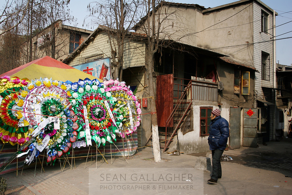 CHINA. Hubei Province. Wuhan. A woman walks past special wreathes that are given on the event of a death. They are placed outside the home of the deceased.  Wuhan (population 4.3 million) is a sprawling city that sits on both sides of the Yangtze River. 2008