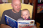 """Bald headed Dad reads to blonde two year old boy book """"Wheels on the Bus"""" sitting in rocking chair at home."""