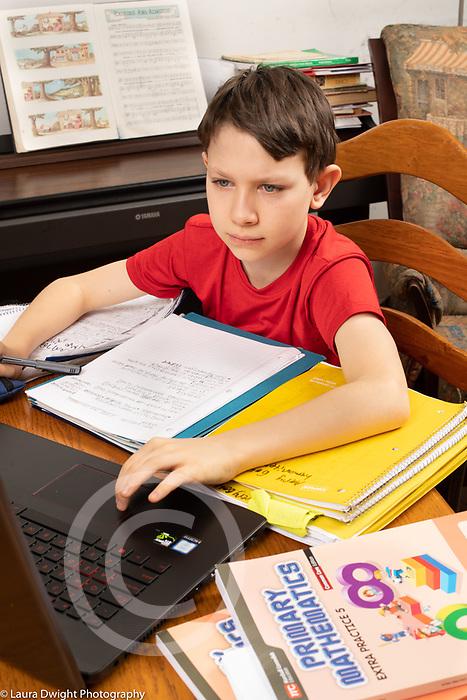 11 year old boy doing homework, using laptop computer
