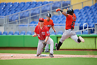 Washington Nationals first baseman Blake Chisolm (14) waits to receive a throw as James Nelson (67) lunges for the base during a Florida Instructional League game against the Miami Marlins on September 26, 2018 at the Marlins Park in Miami, Florida.  (Mike Janes/Four Seam Images)