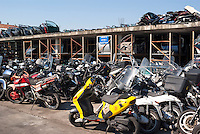Magazzino ricambi e rottami di ciclomotori in uno sfasciacarrozze alla periferia nord di Milano --- Stock of spare parts and scrap mopeds at a car wrecker in the north periphery of Milan