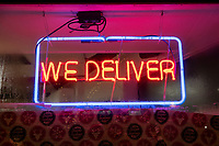 """A neon sign reads """"We Deliver"""" in the window of Dragon Pizza in Davis Square in Somerville, Massachusetts, on Tue., Jan. 26, 2021."""