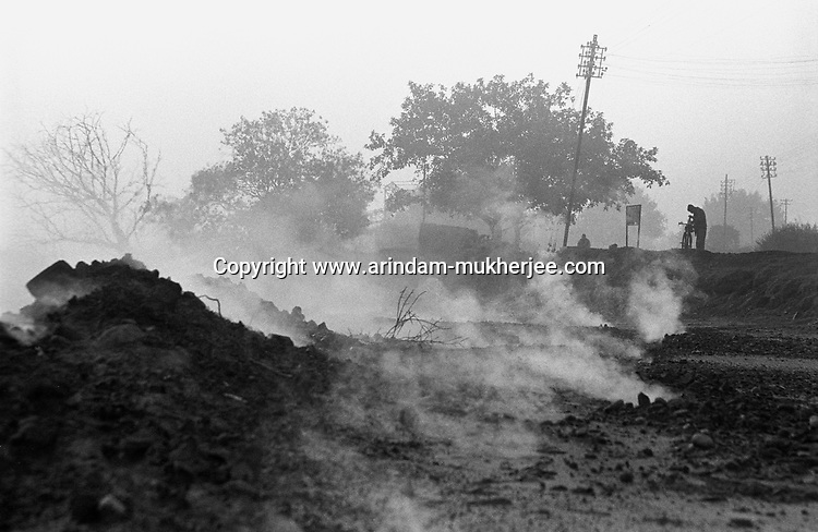 Smoke and poisionous gases coming out of the ground which is originating from a massive mine fire burning for last few decades. Mine fire is a big problem to the Jharia city. This fire is aggrevating towards the city in a very slow pace. All kinds national and international efforts gone in vain in extinguishing this fire, Jharia, Jharkhand, India. Arindam Mukherjee