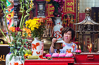 Sin Sze Si Ya Taoist Temple, Chinatown, Kuala Lumpur, Malaysia.  Worshiper Lighting Joss Sticks. Oldest Taoist temple in Kuala Lumpur (1864).