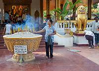 Cambodia, Siem Reap.  Worshiper Placing Incense at Preah Ang Chek and Preah Ang Chorm Temple.