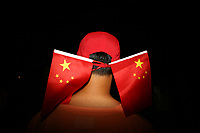 CHINA. Beijing. A man whilst watching the opening ceremony of the Beijing Summer Olympics. 2008