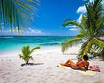 Dominikanische Republik, Isla Saona, Laguna Canto de la Playa, junge Frau liegt allein an einem einsamen Strand, liest Illustrierte | Dominican Republic, Saona Island, Laguna Canto de la Playa, young woman lying at deserted beach, reading