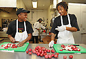 Liberty Kitchen trainees Charles Williams and Jory Adams  prepare lunch for students at the New Orleans College Prop School in New Orleans, Thurs., March 22, 2012.