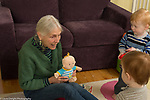20 month old toddler fraternal twin boys with grandmother, talking, holding toy doll, child care, grandmother takes care of them twice a week