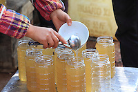 Luoping, Yunnan. The beekeepers put the honey into jars immediately after harvesting it.