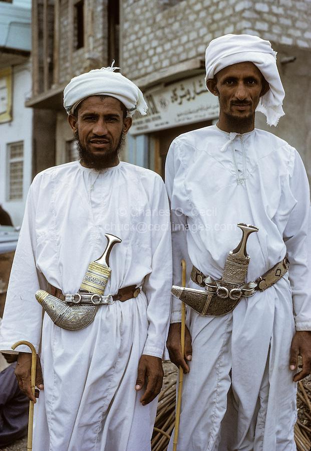 Oman, 1972.  Two Omani Men.  Each wears a dishdasha (white robe), a khanjar (curved dagger), an msarr or massar (head turban), and carries an asa or Khuzran (traditional walking stick).