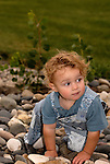 A toddler creeps across the river stones.