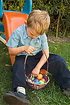 Toddler boy 3+points with his finger to Easter eggs in his basket as he sits on.his slide in the grassy yard counting each egg.