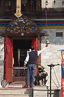 Kathmandu, Nepal.  Nepali Worshippers Ring a Bell at a Temple's Entrance to Drive Away Evil Spirits.  Mahendreshwar Temple, Durbar Square.