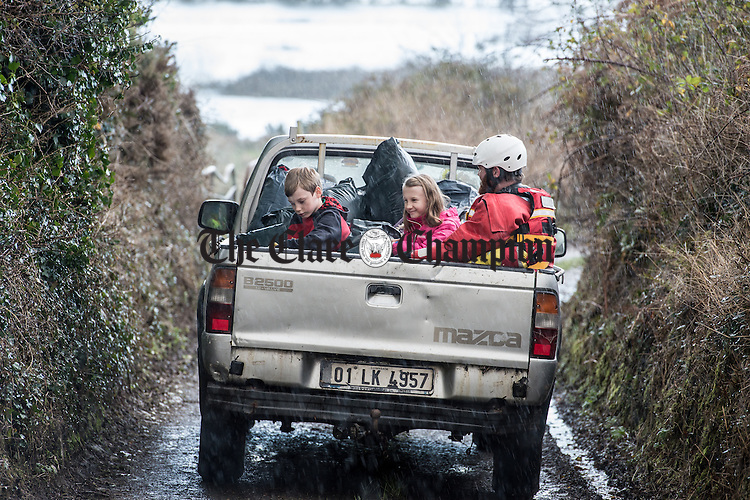 Ten year old twins Jack and Caoimhe Moloney with their dog Lily and 1  make their way to a boat by truck as the family evacuates their home at Doorus. A number of homes at Doorus, O Callaghan's Mills were cut off during the recent heavy rainfall which came with storm Desmond. Photograph by John Kelly.