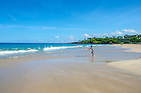 Boy with boogie board running toward ocean at Hapuna Beach, along the Big Island's Kohala Coast. This white sand beach has been rated one of the best beaches in the world time and time again.