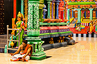 Batu Caves, Hindu Priest Reading in Temple at Base of Steps leading to Caves, Selangor, Malaysia.
