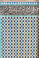Fes, Morocco.  Attarine Medersa, 14th. Century.  Decorative Tile Work in the Darj w Ktaf Motif, under Arabic Calligraphy on Tiles.