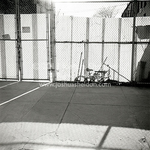 Shadow of bicycle behind translucent fence<br />