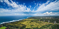 An aerial view of immense, wing shaped clouds over the North Shore area of O'ahu, with windmills on the right.