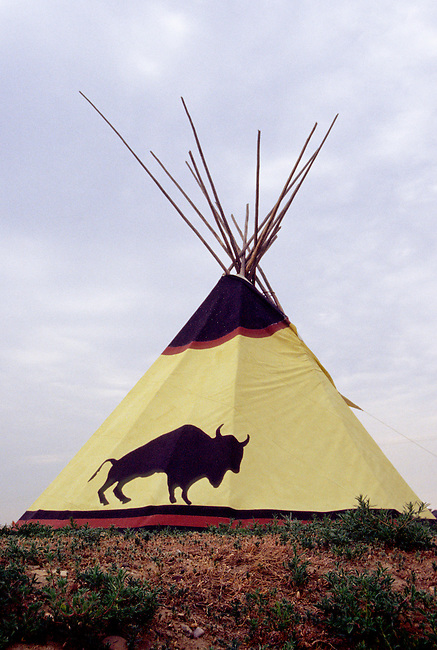 Chippewa-Cree tipi dwelling decorated with a buffalo painted on it's side sits erected on the Great Plains in Montana