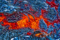 Red glowing coals in a forest slash pile create a natural work of abstract art.