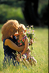 young woman embracing daughter in field with flowers