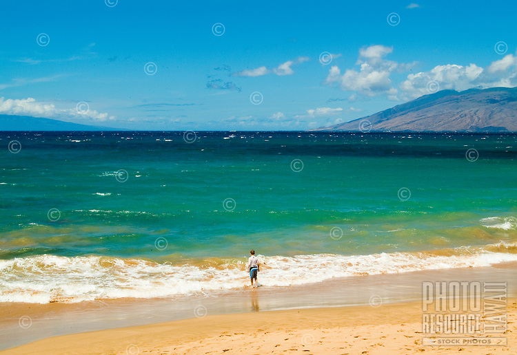 """A swimmer stands at the edge of """"""""Baby or Little Beach"""""""" at Makena. West Maui mountains in background."""