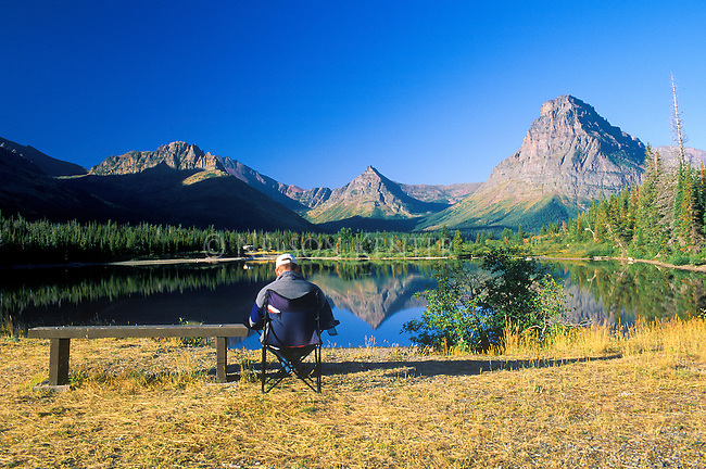 A man enjoys a peaceful moment at sunrise in Glacier National Park on the shore of Pray Lake in the Two Medicine Valley