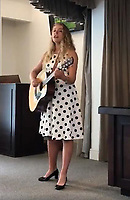 """Pictured: Eve Stewart, one of the granddaughters of Pat Stewart is singing a song in tribute to her grandmother wearing a spotty dress.<br /> Re: The funeral of Pat Stewart at the Cardiff and Glamorgan Memorial Park and Crematorium, Wales, UK. Pat Stewart became famous as """"the girl in the spotty dress"""" after an iconic image taken by Bert Hardy in Blackpool in 1951."""