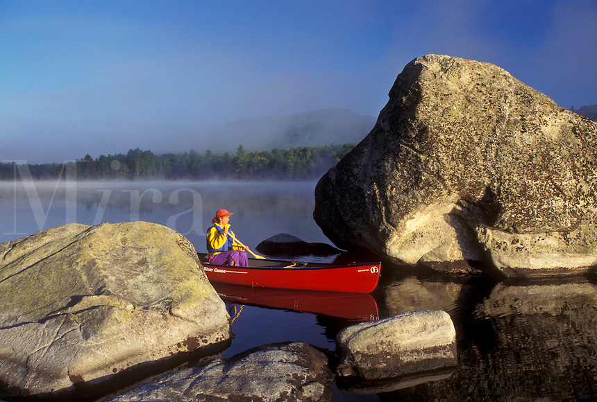 canoeing, canoe, Vermont, VT, Woman paddling a red canoe on Kettle Pond through boulders in the mist in Groton State Forest.