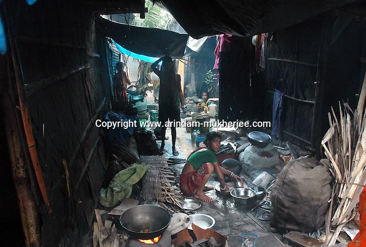 A lady cooking at a slum in Calcutta.