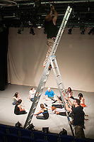 Dance students at the end of  rehearsal for end of year show receiving notes from their director while stage hands fix the lighting, Kingston College.