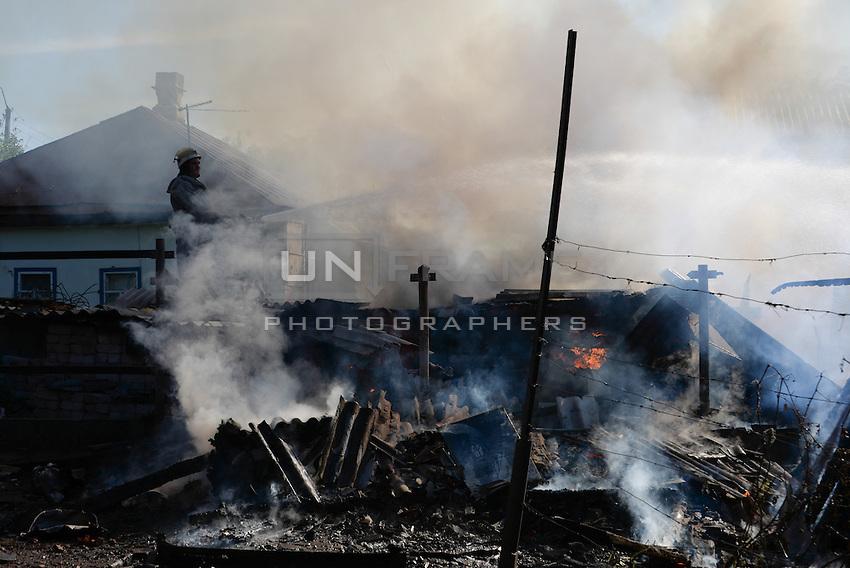 Fire fighters exstinguish houses on flames destroyed by shelling. Slovyansk. Ukraine.