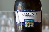 Wine glasses in the tasting room. Bottle of Kameno Vrhunsko Suho Vino white wine from their best vineyard. Detail of label with a picture of the vineyard. Vinarija Citluk winery in Citluk near Mostar, part of Hercegovina Vino, Mostar. Federation Bosne i Hercegovine. Bosnia Herzegovina, Europe.