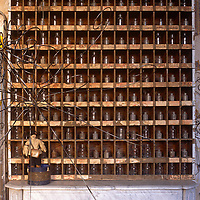 A collection of small glass bottles are arranged neatly in a wooden frame above a marble fireplace.