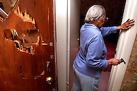 """Beatrice Turner, 89, stands with the .22 caliber pistol she used to fend off an intruder who broke down her front door, left, in the early morning hours.  Turner, who did not want her face shown in this photograph, emerged from her bedroom at rear, fired one shot and missed, then calmed the intruder who was then arrested by Des Moines Police officers who arrived at her northeast Des Moines home.  """"About six officers were here, and they reloaded the gun for me,"""" she said.  """"All of them were hugging me and telling me how brave I was."""""""