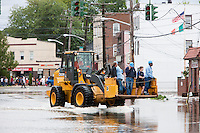 MAMARONECK, NY - AUGUST 28: A Con Edison repair crew gets a lift in a front loader on flooded Mamaroneck Avenue in the Village of Mamaroneck, New York on Sunday August 28, 2011 in the aftermath of Hurricane Irene.  The crew was working to restore electrical power to the area.