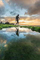 A man walks near a kelp-lined pond at sunset, Pua'ena Point, North Shore, O'ahu.