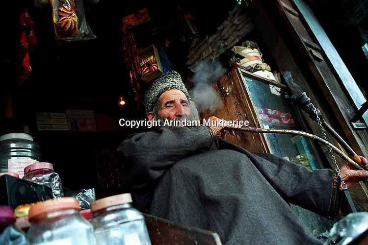 A shop owner smokes the traditional Kashmiri pipe called Jajeer at the market at world famous Dal Lake,Srinagar. Kashmir valley, india