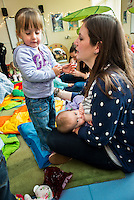 """A mother breastfeeding her baby at a drop-in breastfeeding support centre while talking to her older daughter.<br /> <br /> Image from the """"We Do It In Public"""" documentary photography project collection: <br />  www.breastfeedinginpublic.co.uk<br /> <br /> Dorset, England, UK<br /> 17/04/2013"""