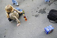 Switzerland. Canton Bern. Bern. A young girl, seated on the concrete ground, drinks a bottle of Feldschlossen beer. A six pack of beer in aluminium cans and a bottle of the alcohol Pesca Frizz  (a mixing of fizzy wine and sugar with a taste of pear) are on the pavement. The woman is a fan of the SCB Bern hockey club. She is outside of the Bern Arena and waits for the doors to open. © 2006 Didier Ruef
