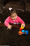 12 month old baby girl standing at table, playing with blocks, stacking on block on top of another