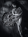 Sensual artistic portrait of a young woman in a dress with bare legs lying on the floor with closed eyes holding a bouquet of wild flowers Black and white Image © MaximImages, License at https://www.maximimages.com