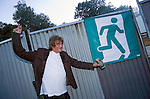 Howard Marks the legendary drugs smuggler poses next to a running man sign at the annual Escape into the Park dance festival in Singleton Park, Swansea.